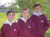 Photo of three young boys wearing jackets with a Griz logo